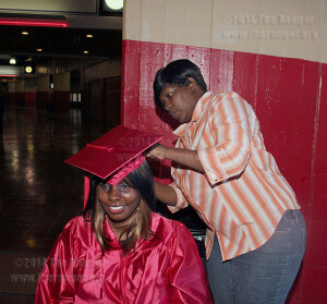 English sophomore Kyle Haley gets help from her sister May 12 before the commencement at Freeman Coliseum.   Photo by Riley Stephens