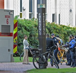 Paramedics and campus police wheel a gurney to an ambulance after a student lost consciousness.