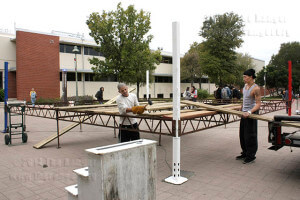 Welder Eric Garcia and kinesiology sophomore Dustin Southichack set up the boxing ring for the Olympic-style boxing event Oct. 26 in the mall. Thunderstorms rained out the event, which was replaced with indoor sparring matches.  Photo by Monica Correa