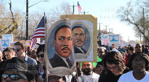 Marchers carry signs of the Rev. Dr. Martin Luther King Jr. during the 2.75-mile march Jan. 19 from Dr. Martin Luther King Jr. Academy to Pittman-Sullivan Park. San Antonio had the largest MLK march in the nation, with more than 175,000.  Photo by Anthony B. Botello