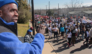 Joe Satterwhite, St. Philip's graduate, records the Martin Luther King Jr. March Jan. 19 from the sidelines of Martin Luther King Drive west of S. Rio Grande. Satterwhite said King's dream is being realized slowly and St. Philip's is more diverse now than when he graduated in 1966.  Photo by E. David Guel