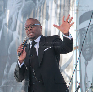 "The Rev. Dr. Marcus Cosby speaks to an audience, referencing scripture and words of the Rev. Dr. Martin Luther King Jr. Jan. 19 after the Martin Luther King Jr. March from the Martin Luther King Jr. Academy at Pittman-Sullivan Park. Cosby quoted King saying ""we have the oportunity to ensure that justice rolls down like waters and righteousness like an everflowing stream.""  Photo by E. David Guel"