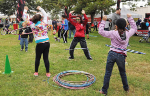 Rose Mary Rodriguez from Radio Disney teaches children to hula hoop during the third annual Síclovía on Sunday at Maverick Park.  Gloria Fernandez De Clements