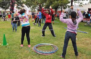 Rose Mary Rodriguez from Radio Disney teaches children to hula hoop during the third annual Síclovía on Sunday at Maverick Park.  Gloria Fernandez De Clements