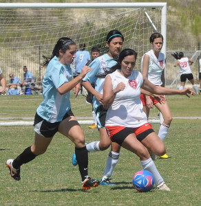 Nursing sophomore Michelle Rodriguez steals the ball from two S. A. Nightmares opponents and tries to make her way to the goal.  Photo by Gloria Fernandez De Clements