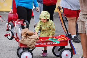 Zoe Duran keeps warm in a wagon full of blankets. Duran spent the day being pulled around the event, getting down to stretch her legs and interact with her parents.  Photo by Samber Saenz