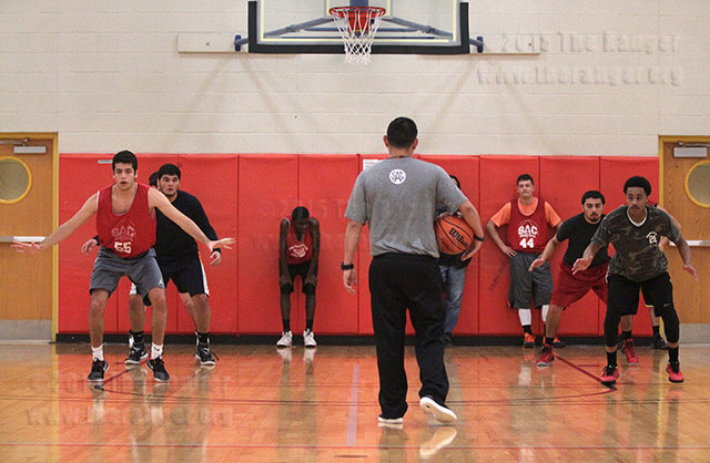 Business management sophomore Chady Joukeh and business freshman Jalen Manriquez perform a footwork drill directed by coach Louis Martinez Thursday during the second day of basketball tryouts in Gym 2 of Candler.  Photo by E. David Guel