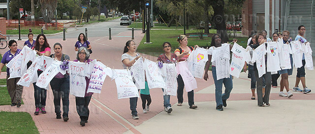 Non-Traditional Student Club members join for a clothesline walk for Domestic Violence Awareness Month Oct. 23 north of Oppenheimer. Club members walked from the empowerment center to Loftin.  Photo by Sergio Ramirez