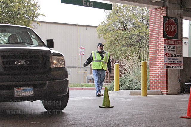 Parking attendant Roy Ramirez helps to guide vehicles to the correct parking spaces Thursday, in the parking garage.  Photo by Riley Stephens