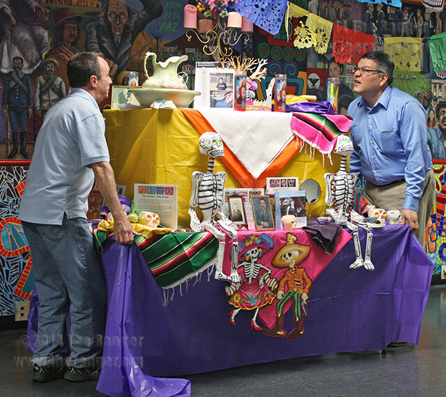 Mortuary science freshman Michael Hall and Professor Francisco E. Solis carry a decorated altar to the middle of the stage during the Day of the Dead workshop Nov. 1 in Loftin. It has been a tradition in the department to bring awareness to the way death is viewed in the Mexican culture.  Photo by Carolina Vela