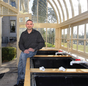 Bradlee LaBrutta, business management sophomore and president of Enactus, poses with grow beds in a hydroponic garden in the greenhouse Thursday at Koehler. Filtered water flows from fish tanks into plant beds, then to bio-filters, a subtank, then back again. E. David Guel