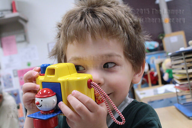 William Chapman, 2, is all smiles with his camera after nap time Wednesday in Room 0.1 at the early childhood center.  Photo by Anthony B. Botello