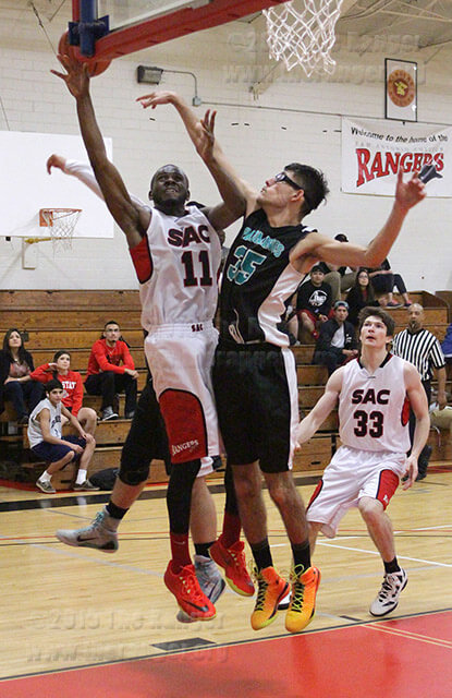 Kinesiology freshman Andrew Butler puts up a contested shot through pre-nursing freshman Ricardo Garcia in the first half Wednesday.  Photo by E. David Guel
