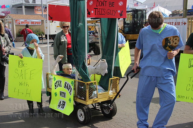 "Representing the 4-H Club, Ethan Colglazier, 14, drags a hospital bed wagon with Mason Colglazier, 14, in it as ""Accident Al"" and Hope Barry, 8, alongside the wagon. 4-H provides awareness for home safety and promotes kids developing heart, head, hands and health to better their communities.  Photo by Vanessa Frausto"