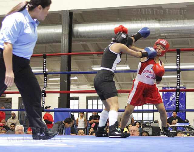 "Liberal arts sophomore Maria Giron takes a hit in the second bout of the San Antonio Regional Golden Gloves Tournament preliminaries Feb. 20 in the Woodlawn Gym. The official of this bout was Cynthia Trejo, and Giron was categorized as a female novice 101-pound lightweight. Although her bout did not qualify her for the next competition, she said, ""Overall I tried my best."" The local tournament benefits Boys & Girls Clubs of San Antonio.  Photo by Tress-Marie Landa"