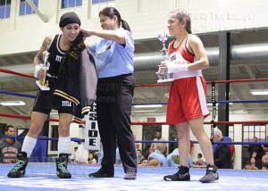Official Cynthia Trejo awards Lynzee VillaFranca a championship trophy and windbreaker after defeating liberal arts sophomore Maria Giron by decision during the preliminaries of the San Antonio Regional Golden Gloves Tournament Feb. 20 at the Woodlawn Gym.  Photo by Tress-Marie Landa
