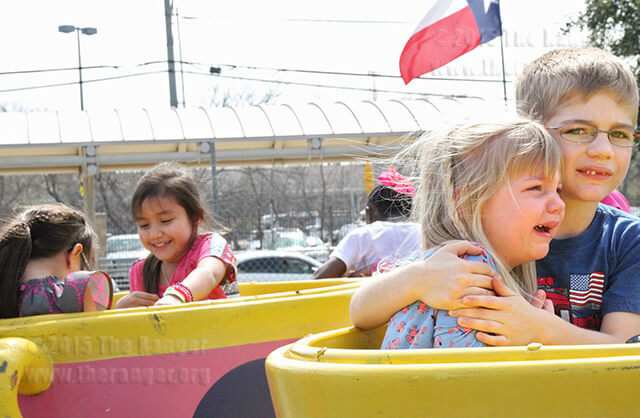 Gavin Swihart, 6, wraps his arms in protection around his sister Avert Swihart, 3, while riding the Crazy Daisy Cup. Avert said she just wanted to get off the ride while Gavin got back on without her.  Photo by Gwendolyn Garcia