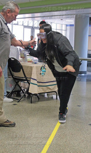 Officer Charlie McLennen with the ACCD crime prevention unit assists nursing sophomore Gianina Ledesme as she attempts to maintain her balance using simulator goggles.  File