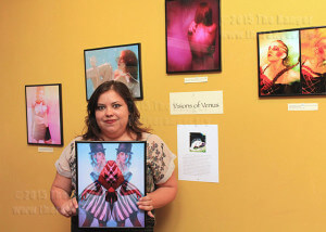 "Angela Ramos, owner and photographer of Raven Red Photography, holds one of her images displayed during Tobin Hill's ""Art on the Hill""  Sept. 2011.  File photo"