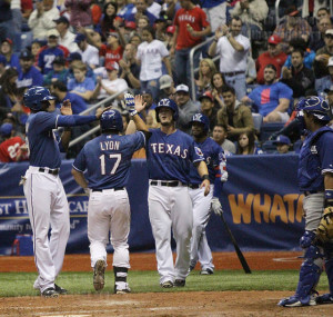 Rangers catcher David Lyon celebrates with first baseman Trever Adams after hitting a three-run homerun in the bottom of the eigth inning of an exhibition game against the Los Angeles Dodgers as part of the H-E-B Big League Weekend March 21 in the Alamodome.  Photo by E. David Guel