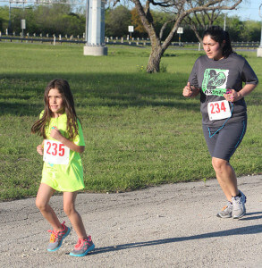 Alanah McAlhaney, 7, and kinesiology sophomore Linda McAlhaney run the 5k. Linda has ran many 5k's and thought this would be a good experience for her daughter. This was Alanah's first 5k.  Photo by Vanessa Frausto