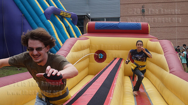 Criminal justice sophomore Cody Sanders and art sophomore Maddie Mason compete in the bungee cord races, hosted by the Business Student Organization, April 24 at Northwest Vista's 20th Birthday Celebration. The objective of the race is to place a velcro wrapped bean bag as far away from the starting point before the bungee cord pulls the participant back. Sanders won every round.  Photo by Tyrin Bradley