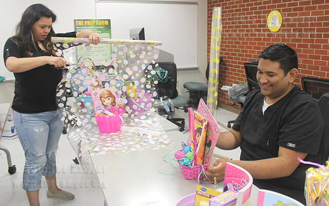 Mortuary science sophomores Cecilia Lopez and John Adam Segura wrap Easter baskets for the Children's Shelter March 25 in Room 234 of Nail. This was the department's first year donating to the shelter, and they exceeded their goal of 60 baskets with 105. The baskets were delivered to the shelter March 26.  Photo by Vanessa Frausto