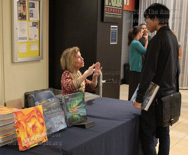 "Photography sophomore Yuki Takahata of this college buys and gets signed his own copy of ""Simply Beautiful Photographs,"" a book by Annie Griffiths, at her presentation ""Changing The World, One Photograph At A Time"" Monday at UTSA.  Photo by Anthony B. Botello"