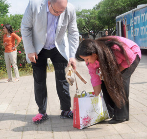 President Robert Vela picks out a change of shoes with the aid of Gracie Savage, administrative assistant in student services. Vela wore brown wedges to lead the march.  Photo by Jon Hernandez