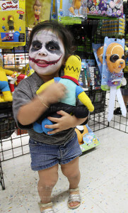 Jaydee Deluna, 2, grabs a Homer Simpson doll at the Heroes and Fantasies comic book store. Deluna, whose face is painted like the Joker character from DC Comics, took a photo with him at the event.  Photo by Cynthia M. Herrera.