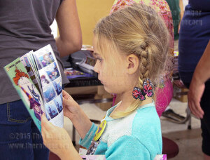 Elizabeth Williamson, 4, reads one of the free comic books given out during Free Comic Book Day at Heroes and Fantasies.   Photo by Cynthia M. Herrera.