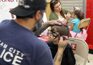 Ramon Barajas, 4, has his face painted by artists from Beyond the Canvas at the Free Comic Book Day event at Heroes and Fantasies comic book store. Ramon dressed up as Batman for the event.  Photo by Cynthia Herrera
