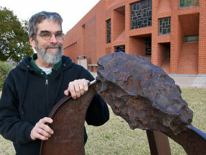 Brother Guy Consolmagno stands next to a statue of a meteorite at his alma mater, the University of Arizona.  Courtesy
