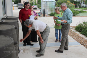Steven Lewis, continuing education program director, explains EcoCentro's rain water collection process April 22. Five smaller barrels hold 200 gallons each and are available for residential use. The larger well holds 2,700 gallons.  Photo by Mandy Derfler