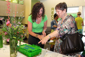 """Project coordinator Leslie Kropf serves ESL adjunct Maureen Kenney """"Happy Bearthday"""" cake for EcoCentro's one-year anniversary and Earth Day April 22. Kropf works with students and volunteers in the garden, which was the source of the flowers on the table.  Photo by Mandy Derfler"""