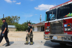 The crew of Fire Station 6 cool off at noon Thursday after putting out a welding fire at 1819 McCullough, two blocks east of this college. Capt. Eric Ruiz said there were no civilians or fire personnel injured and estimated $10,000 in damages to the unoccupied commercial building. Photo by Kyle R. Cotton