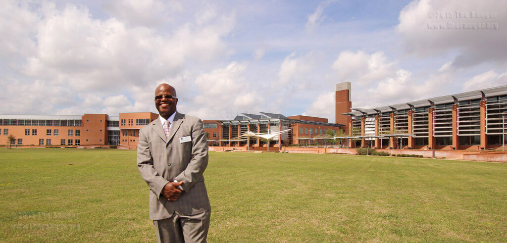 Dr. Craig Follins, president of Northeast Lakeview College, stands in front of the NLC library on the campus green March 2014. File