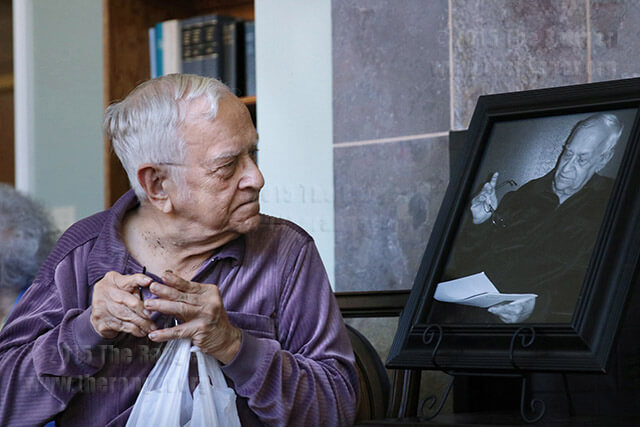 John Igo, retired English professor from this college, looks at the portrait that will hang in the John Igo Health and Wellness Resource Center in the Sun Room at Brookdale Hamilton Wolfe Senior Living at 5331 Hamilton Wolfe Road. Photo by Kyle R. Cotton