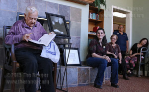 "John Igo reads over ""Easy Reference Guide for Symptoms"" at the unveiling of the John Igo Health and Wellness Resource Center. Igo gave the book to Katie Dale (center right), resident programs director at Brookdale Hamilton Wolfe Senior Living, as a symbol of his donation of more than 250 medical books Sept. 23 in the Sun Room at Brookdale at 5331 Hamilton Wolfe Road. Photo by Kyle R. Cotton"