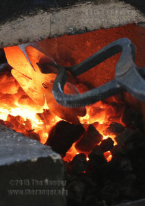 Homemade tongs turn a steel clover to soften the metal for molding. The forge can get up to 3,000 degrees Fahrenheit, about the melting point for steel. The ideal temperature to heat the metal for molding is between 500-1,500 degrees. Photo by Kyle R. Cotton