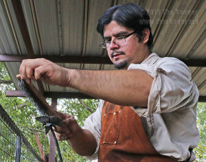 Anthropology sophomore Alex Ruiz carefully brushes and looks over his steel rose for slag caused by the heating process in the forge. This is the final step of Ruiz'z process as his vision comes to life. Photo by Kyle R. Cotton