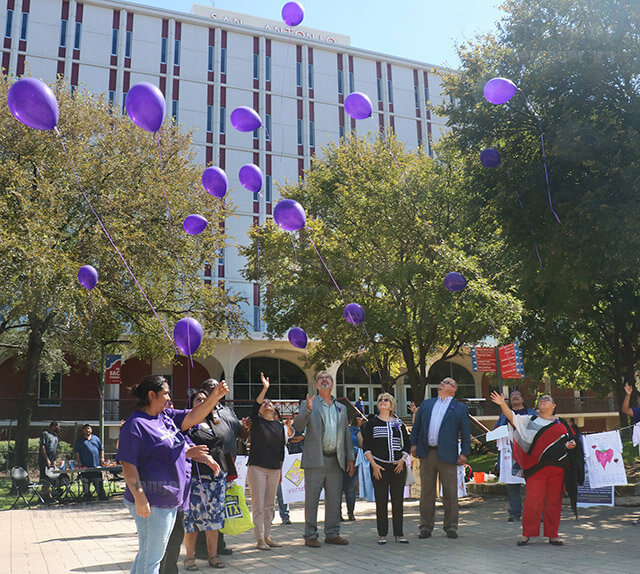 Sandra Nickelberry, Nontradtional Students Club president, instructs administration to release purple balloons, the color that represents domestic violence, in honor of survivors and victims of domestic violence Oct. 12 in the mall west of Moody Learning Center. Survivors and their families were invited to paint shirts, which came in various colors representing different forms of domestic violence, and march together across campus in solidarity.  Photo by Zachary-Taylor Wright