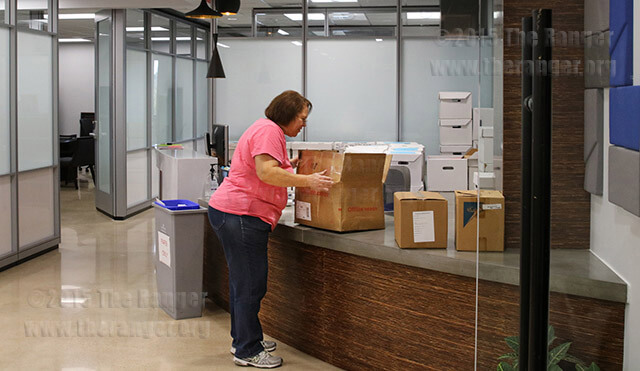 Janet Lozano, administrative assistant to the president, helps move some President Robert Vela's belongings into his newly renovated office on the third floor of Fletcher Friday afternoon. Photo by Kyle R. Cotton