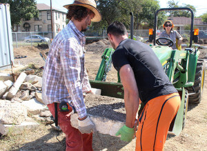 Volunteers David Cantu and Bill Richardson move boulders onto a tractor to use as dividers for the soil Oct. 17 at Garden Day at EcoCentro. The boulders are used as a divider for the landscape on the center's community garden bed. Photo by TiffanyAnne Bermea