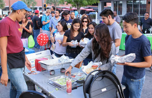 Engineering freshman Itzel Mendoza and business freshman David Davila fill their plates Oct. 6 during this college's first National Night Out hosted by the Alamo Colleges police department on West Evergreen and North Main. Burgers were provided at no cost by Luther's Cafe. Photo by E. David Guel