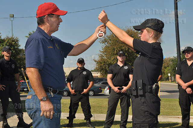 Law enforcement trainee Shanon Wright is handcuffed by Instructor Bobby McMillan in a handcuffing exercise during Private Security Training at the law enforcement training center. File