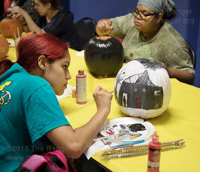 Math freshman Ingrid Zamora concentrates on painting her pumpkin for the decorating contest hosted by the Campus Activities Board Oct. 24 in the Fiesta Room of Loftin. There will be one winner for each category, creative/original, funniest and scariest, who will receive a Kindle Fire. The winners will be announced at Screamfest, this college's Halloween festival 9 a.m.-2 p.m. today in the mall. Photo by Josue Hernandez