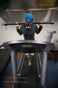 Kinesiology sophomore Roel Gonzalez carries a 25-pound bar on an inclined treadmill and wears an elevation mask set to 5,000 feet above sea level Sept. 22 in the gym in Candler. Running is his coping mechanism for dealing with the effects of post-traumatic stress disorder. Photo by Daniel Carde