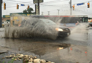 A vehicle plows through a large puddle Oct. 30 along San Pedro Avenue past West Cypress. Parts of San Antonio are under fash flood watch until 1:30 p.m. today. Sidewalks and roads remain hazardous as scattered thunderstorms are expected until Halloween. Photo by E. David Guel