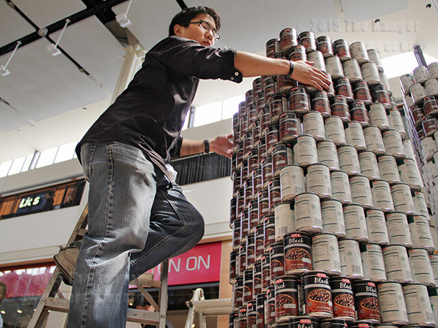 Architecture sophomore Michael Chang aligns cans to keep the structure stable. The structure has no internal support. Monica Lamadrid